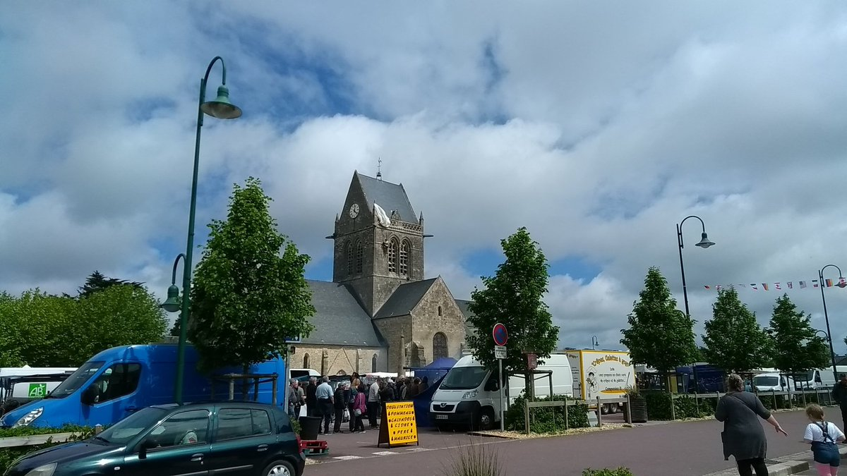 Market day in Ste Mere Eglise, with dummy US paratrooper hanging from the church tower (photo: James Kemp)