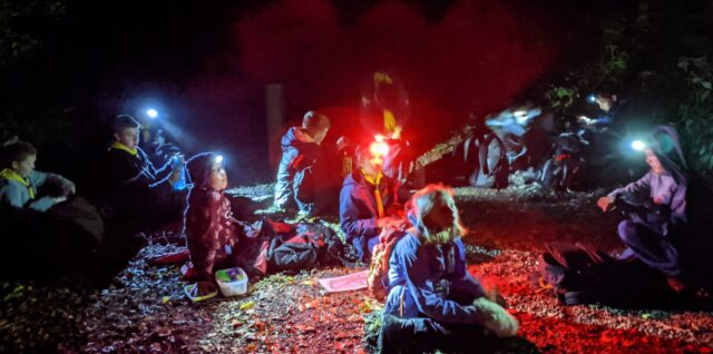 A group of scouts on a night navigation exercise stopped for a break